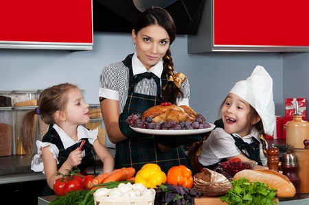 mother with two daughters in the kitchen preparing Christmas dinner with turkey and vegetables photo