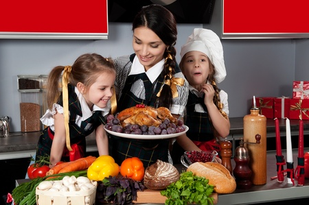 mother with two daughters in the kitchen preparing Christmas dinner with turkey and vegetables Stock Photo - 11249076