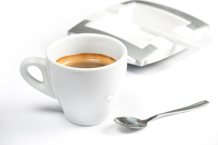 espresso coffee in a white cup with a spoon on a white background  ashtray with a cigarette in the background photo
