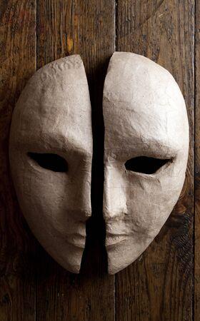 pantomima: dos mitades de las máscaras de papel sobre un fondo de madera