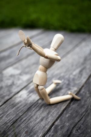 marioneta de madera: muñeco de madera con una cuerda atada a sus manos en las rodillas