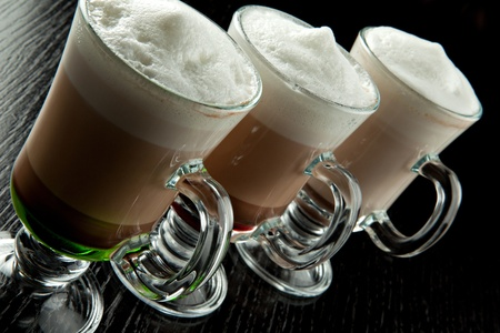 A group of three glasses of hot layered alcoholic cocktails, decorated with milk foam on black bar counter photo