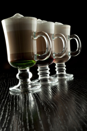 three layered: A group of three glasses of hot layered alcoholic cocktails, decorated with milk foam on black bar counter Stock Photo