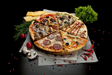 six slices of pizza with different toppings on a wooden board on black background