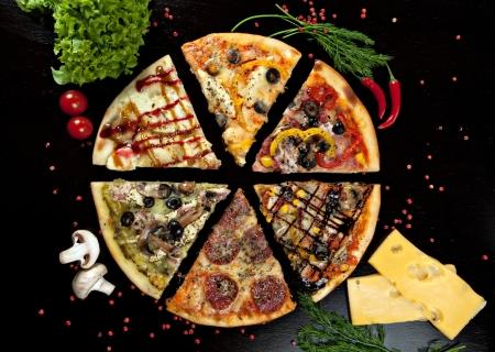 Sechs Stücke Pizza mit verschiedenen Toppings auf einem schwarzen Hintergrund Standard-Bild - 15472097