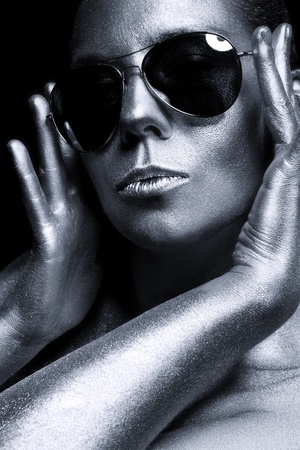 portrait of a beautiful girl with silver skin in sunglasses photo