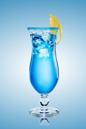 edge of the ice: alcoholic cocktail  Blue Lagoon  with ice on blue background  The edge of the glass is decorated with lemon and blue sugar Stock Photo