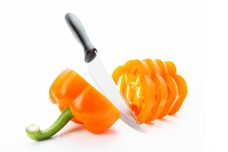 sliced orange pepper sharp knife on a white background photo
