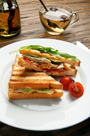 Deli: breakfast is served  Classic White bread sandwich with chicken, cheese, tomatoes, green salad, decorated with arugula on a white plate