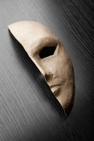 comedy tragedy: Half of the paper masks on a wooden background Stock Photo