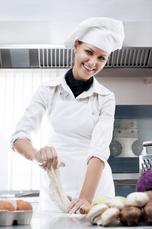 Professional female chef knead the dough for making bread in a professional kitchen