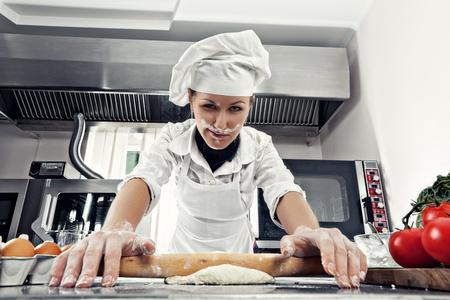 haciendo pan: Cocinera profesional extiende la masa para hacer pan en una cocina profesional. Polvo de harina en la cara Foto de archivo