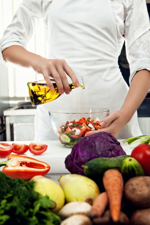 Professional female chef dressing salad with olive oil in a professional kitchen photo