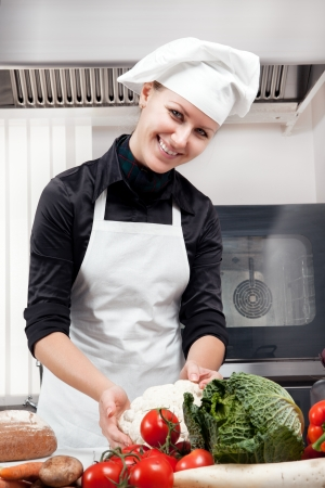 Professional female chef focused on the selection of vegetables for cooking photo