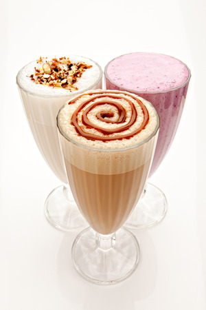 three glasses of milkshakes, caramelshakes and berryshakes cocktails on a white background