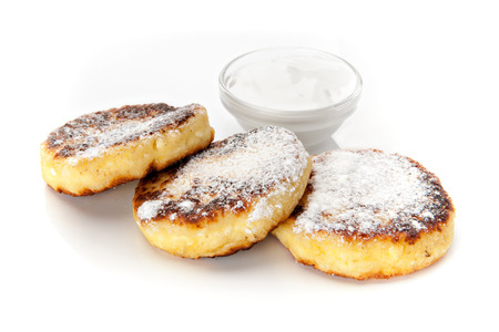 Cheesecakes with sour cream sprinkled with powdered sugar on a white background
