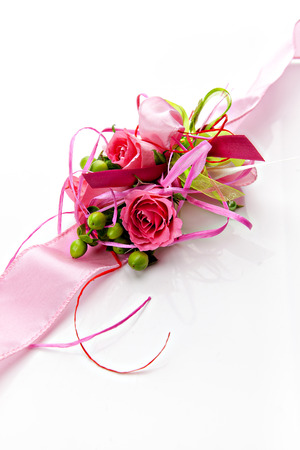 buttonhole: boutonniere of pink roses on a pink ribbon on a white background