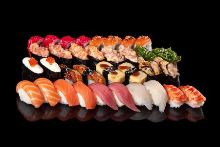 set of sushi rolls and sashimi on a black background