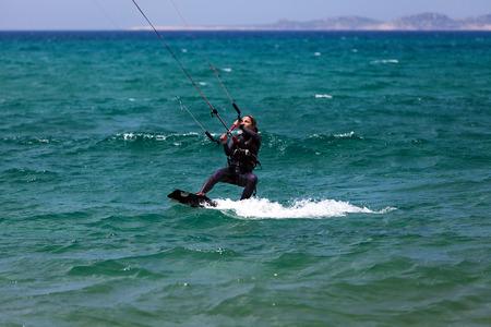 A young woman kitesurfer rides in greenish-blue sea photo