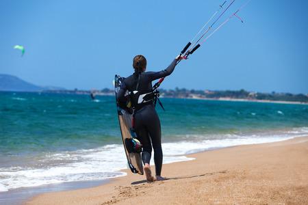 A young woman kitesurfer walking on a tropical beach photo