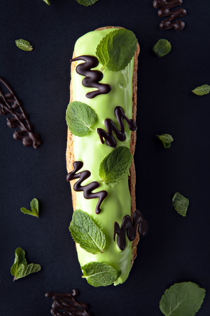 exquisite cream dessert eclair with fresh mint leaves photo