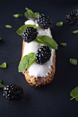 exquisite cream dessert eclair with blackberry and fresh mint leaves photo