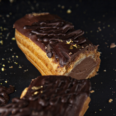exquisite cream dessert eclair sprinkled with chocolate photo