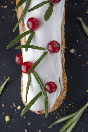 exquisite cream dessert eclair with redcurrant and fresh rosemary leaves photo