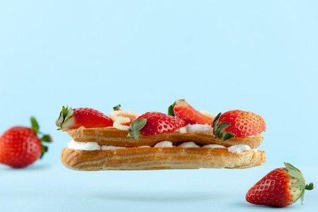 exquisite cream dessert eclair with fresh strawberry photo