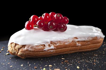 exquisite cream dessert eclair sprinkled with fresh redcurrant photo