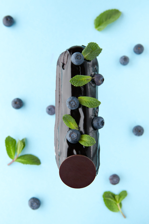 exquisite cream dessert eclair with blueberry and fresh mint leaves photo