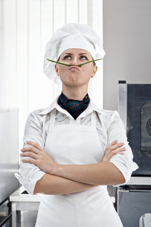 Professional female chef with a mustache of green onion copies of Salvador Dali