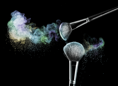 Two makeup brushes with powder on a black background Stock Photo