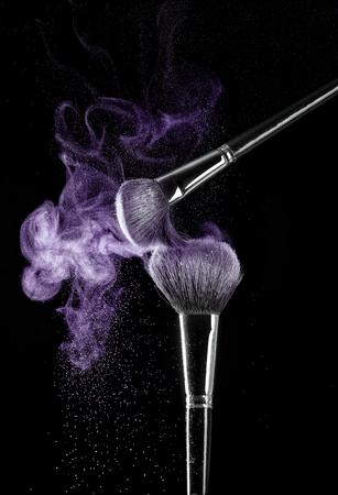 Two makeup brushes with powder on a black background Standard-Bild