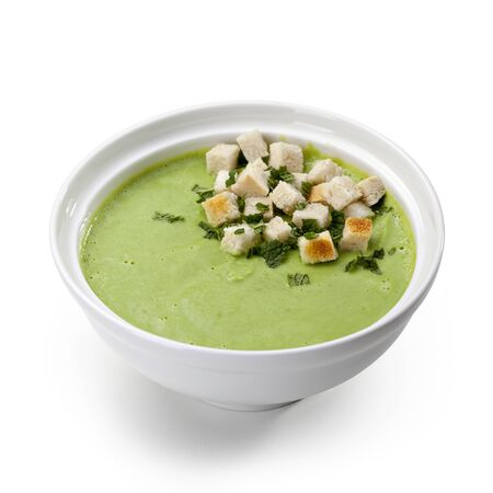 croutons: Bowl green soup puree with croutons on a white background Stock Photo
