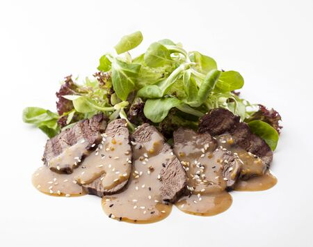 mouthwatering: delicious beef steak with green salad and sauce on a white background Stock Photo