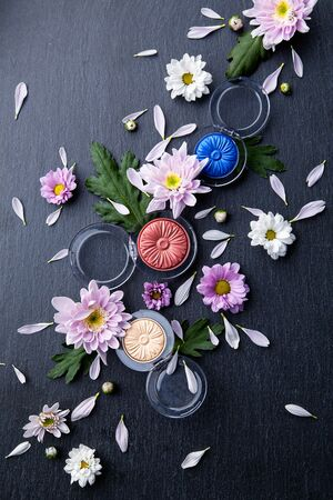 cosmetics products: eyeshadows in three colors are mixed with fresh flowers on a black background slate