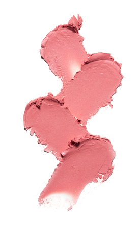 Collection of pink smear crushed cosmetic products on a white background