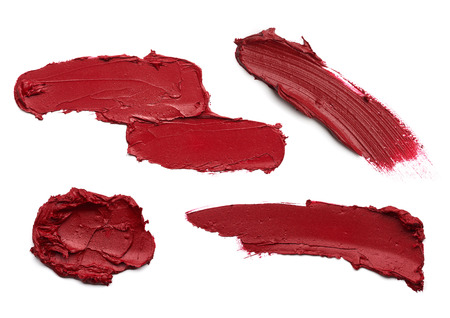 smudge: smear paint of red cosmetic products on a white background
