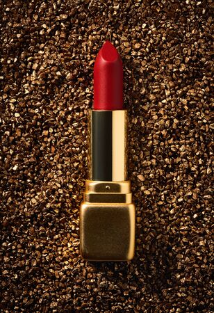 classic red lipstick in a gold case on a gold non-standard background