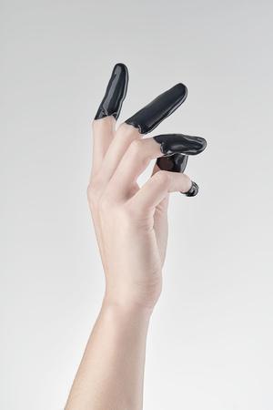 Female hand in liquid black oil or paint