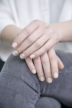Elegant womens well-groomed hands with gentle manicure in white shirt Banco de Imagens