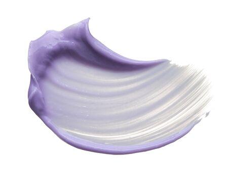 Frotis de maquillaje púrpura de brillo de labios aislado sobre fondo blanco. Textura crema púrpura aislado sobre fondo blanco. Foto de archivo