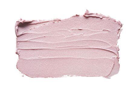 Frotis de maquillaje rosa de base cremosa aislado sobre fondo blanco. Fondo de textura de base cremosa rosa