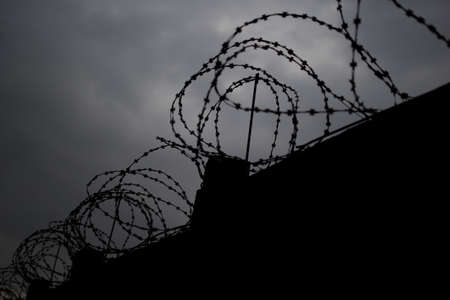 grey  sky: Fence with barbed wire in front of dark grey sky. Selective focus.