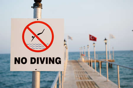 no diving sign: No Diving warning sign in front of Turkish pier.