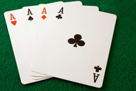 Card hand of four aces on a green felt surface Banco de Imagens