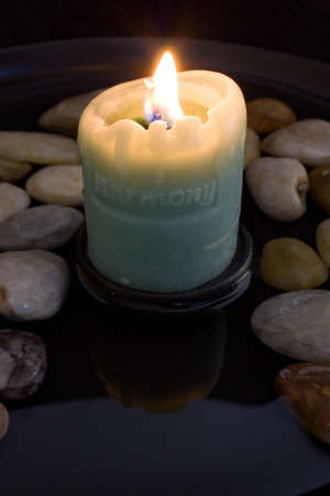 Lit harmony candle reflected in a peaceful pool of water surrounded by smooth stones. Banco de Imagens