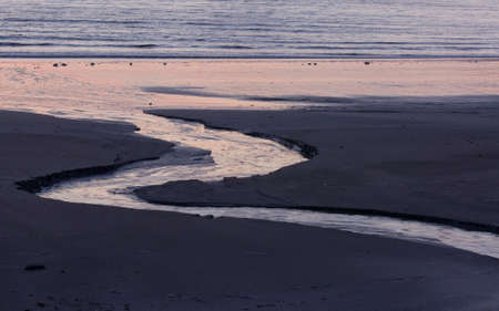 A stream of water naturally cut into the sand running into the ocean