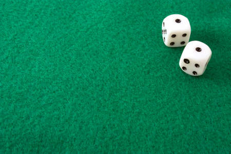 Dice rolled to snake eyes, or double ones, on a green felt table